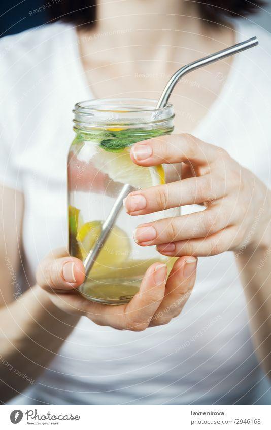 Frau hält ein Maurerglas mit frecher Zitrone und Minzwasser. Trinkhalm Metall Zitrusfrüchte Fokus selektiv Frühstück Getränk trinken Minze Limone Wasser