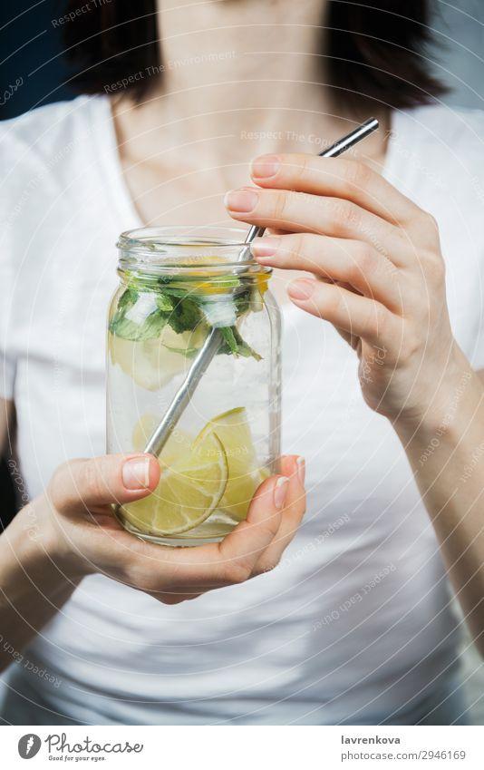 Frau hält ein Maurerglas mit frecher Zitrone und Minzwasser. Trinkhalm Metall Zitrusfrüchte Fokus selektiv Frühstück Getränk trinken Minze Limone Wasser Hand