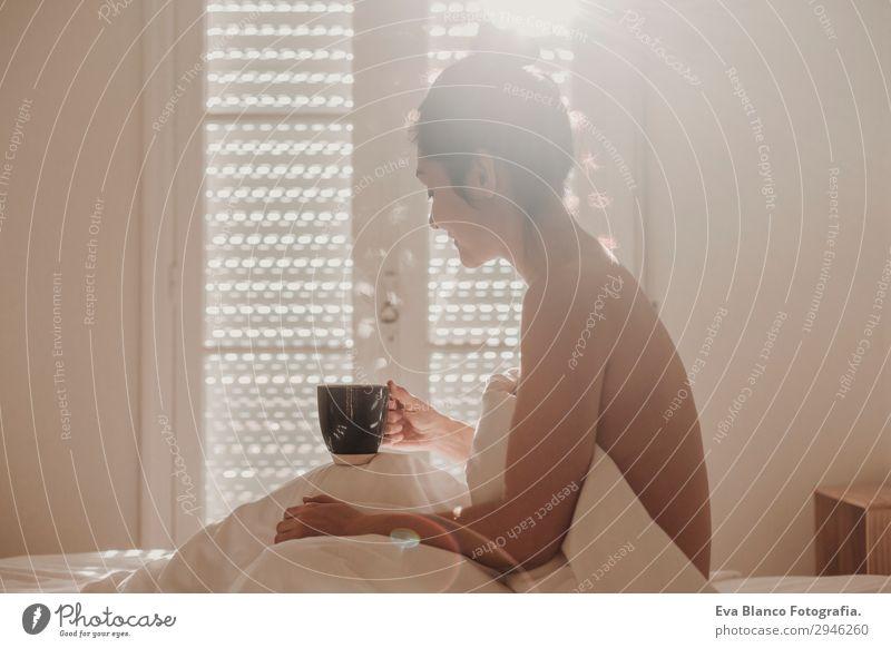 Frau im Bett bei einer Tasse Kaffee. Morgens Getränk Lifestyle Glück schön Körper Erholung Freizeit & Hobby Sonne Wohnung Haus Raum Schlafzimmer feminin
