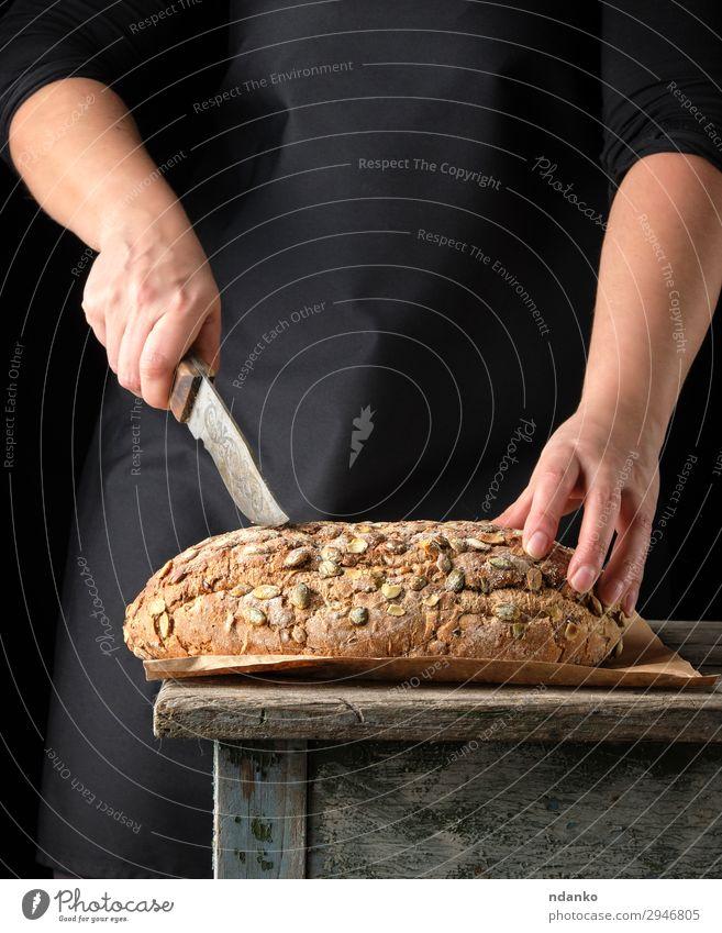 Frauenhände halten ovales, gebackenes Roggenbrot. Teigwaren Backwaren Brot Brötchen Ernährung Essen Frühstück Messer Tisch Küche Erwachsene Hand Wärme Holz