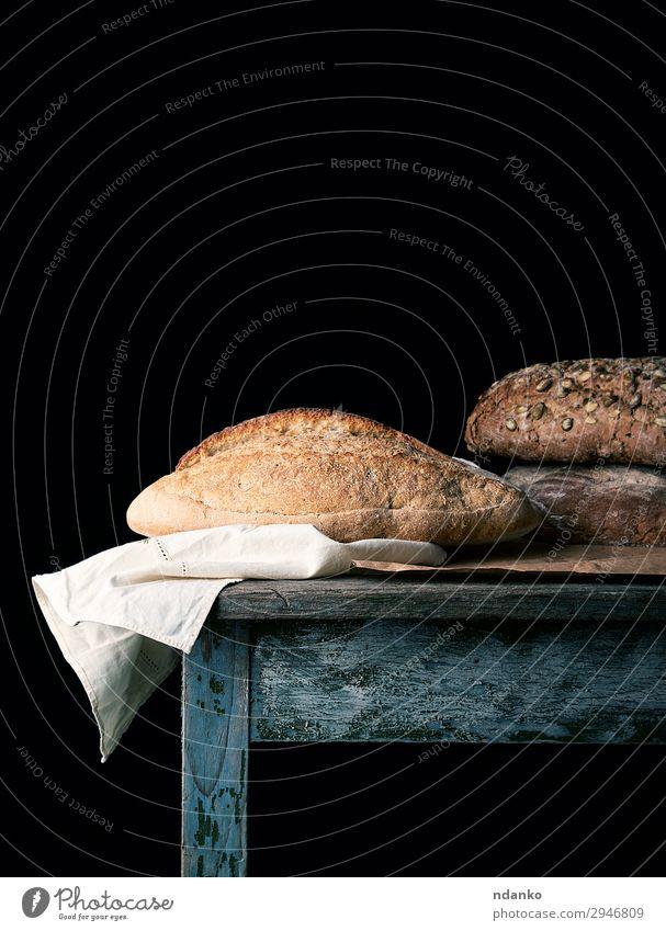 gebackene Brotlaibe auf einem Holztisch Ernährung Essen Frühstück Diät Tisch dunkel frisch lecker natürlich braun schwarz weiß Tradition Bäckerei beige