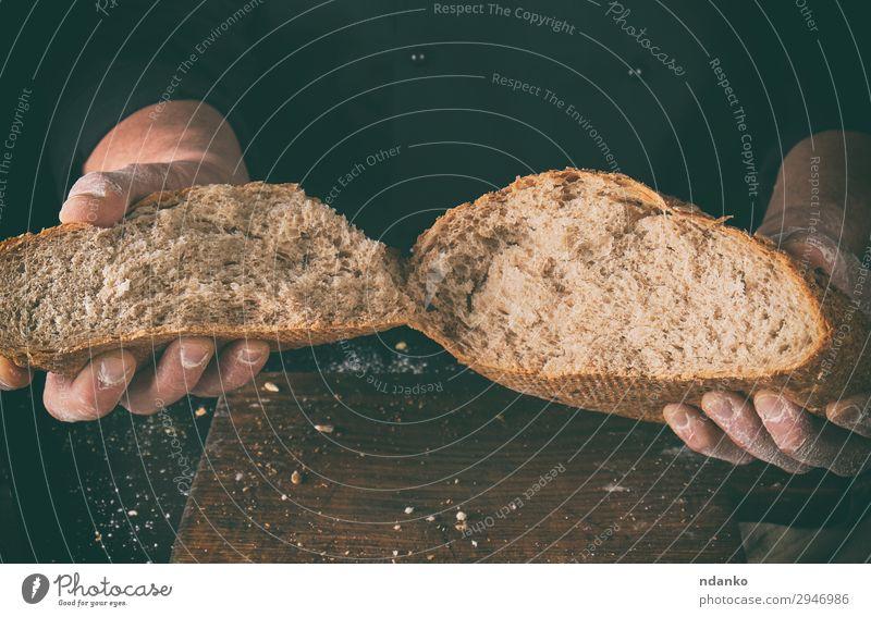 abgebrochenes knuspriges Brot, gebacken aus Roggenmehl Ernährung Tisch Küche Koch Mensch Hand Finger Holz machen dunkel frisch braun schwarz weiß Tradition Korn