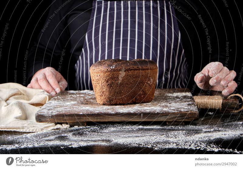 gebackenes Roggenbrot auf einem braunen Holzbrett Brot Ernährung Essen Mittagessen Abendessen Diät Tisch Küche Koch Mann Erwachsene Hand machen dunkel frisch
