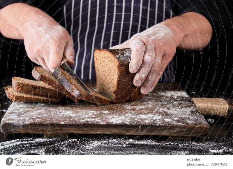 Koch in schwarzer Uniform hält ein Küchenmesser. Brot Ernährung Essen Mittagessen Abendessen Messer Tisch Mann Erwachsene Hand Holz dunkel frisch lecker