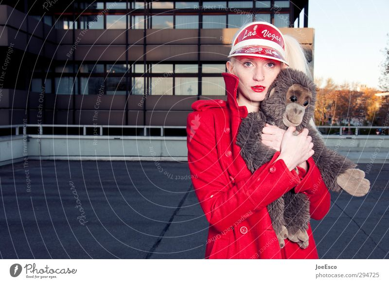 Junge frau im roten Mantel drückt ihr Kuscheltier einen kleinen Affen an sich und schaut in die Kamera.. Stil Freizeit & Hobby Abenteuer Frau Erwachsene Leben