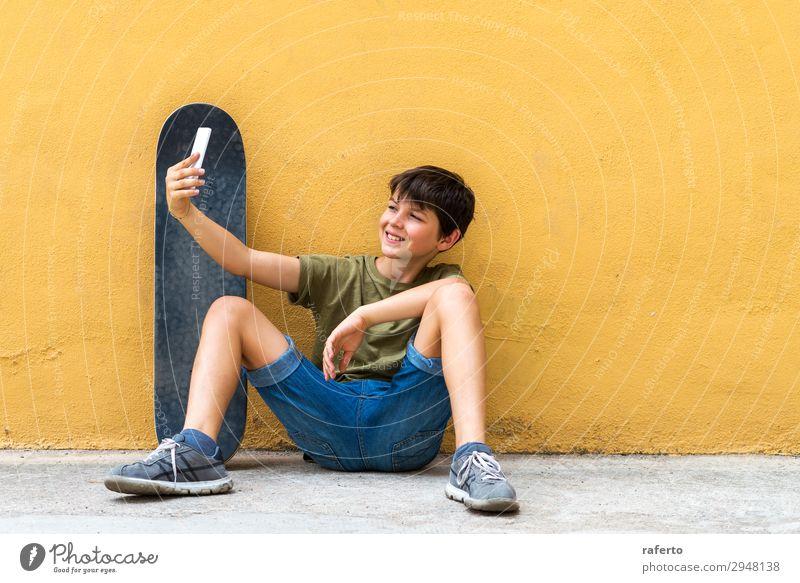 Junge, der auf dem Boden sitzt und sich an eine Wand lehnt und einen Selfie nimmt. Glück Kind Telefon PDA Technik & Technologie Mensch Jugendliche 1 13-18 Jahre