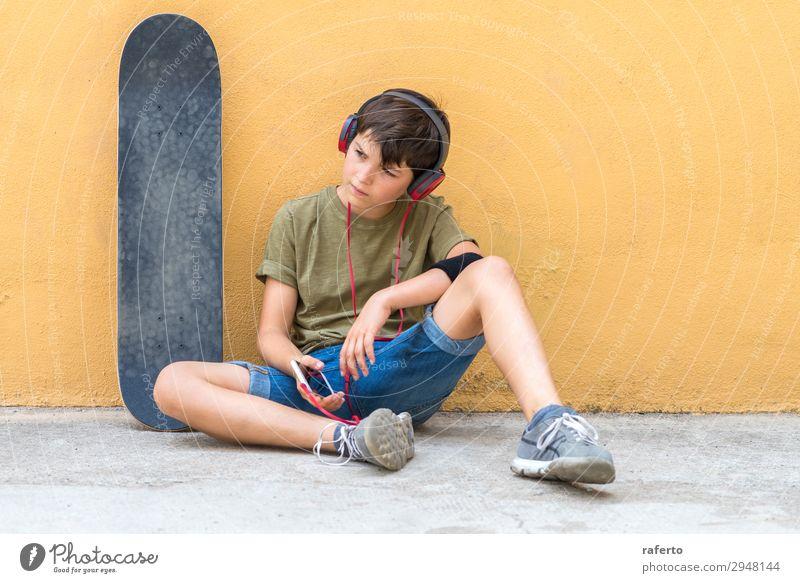 Junge sitzt an einer gelben Wand und hört Musik über Kopfhörer. Lifestyle Stil Glück schön Freizeit & Hobby Freiheit Telefon Headset PDA Technik & Technologie