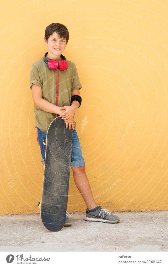 Kleiner Junge, der sich an eine gelbe Wand lehnt und Kopfhörer am Hals hat. Stil Musik Kind Telefon PDA Mensch maskulin Junger Mann Jugendliche Erwachsene 1