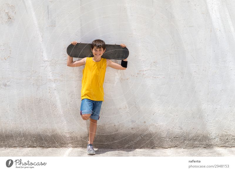Junger lächelnder Junge, der sich an eine gelbe Wand lehnt und ein Skateboard hält. Stil Glück Kind Mensch maskulin Junger Mann Jugendliche 1 Schönes Wetter
