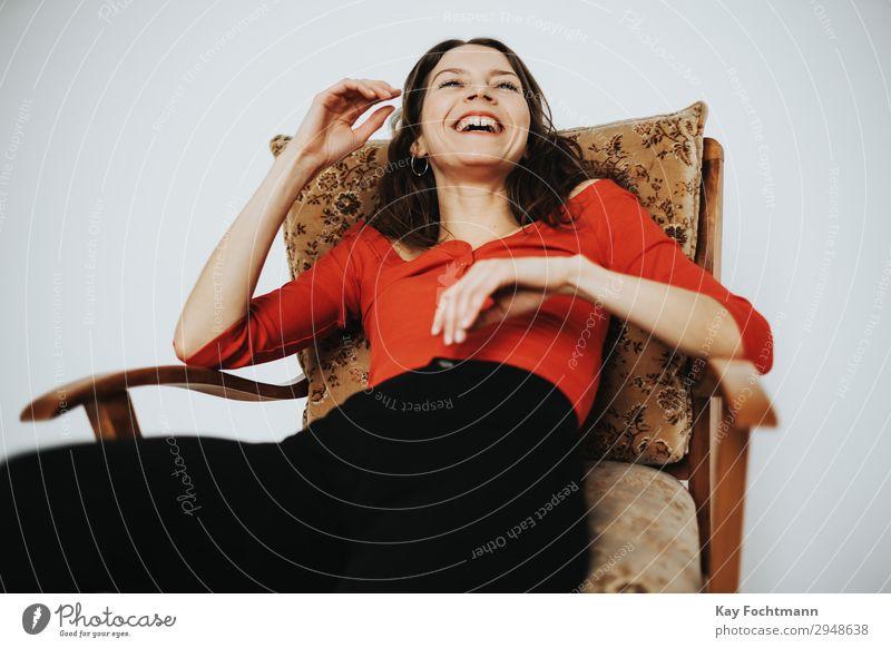 Frau sitzt im Sessel und lacht Lifestyle Zufriedenheit Häusliches Leben Wohnung feminin Junge Frau Jugendliche Erwachsene 18-30 Jahre T-Shirt Hose brünett