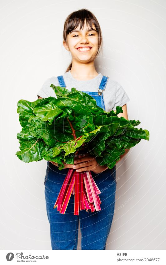 Glückliches Mädchen hält einen Haufen Mangold. Gemüse Ernährung Vegetarische Ernährung Diät Freude Kind Blatt Lächeln frisch natürlich grün rot weiß
