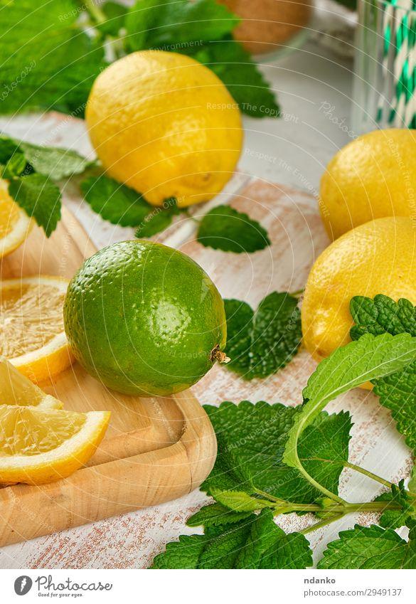 reife gelbe Zitronen und Limetten, minzgrün Frucht Erfrischungsgetränk Limonade Saft Tisch Blatt Holz oben saftig braun weiß Haufen Zitrusfrüchte Cocktail