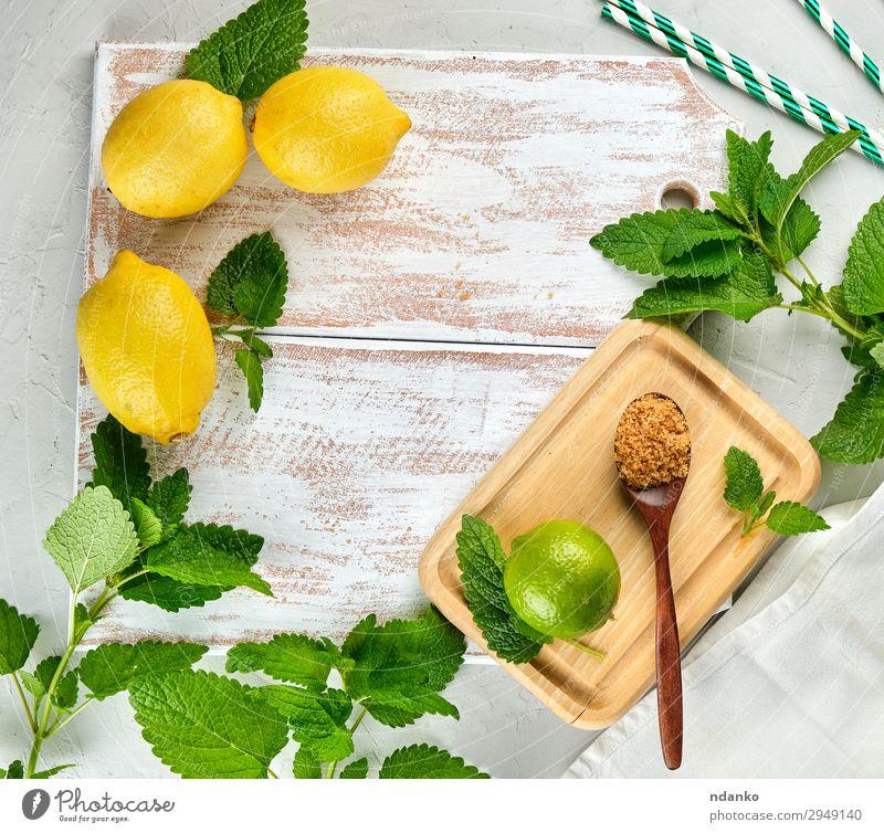 ganze Zitronen und Limetten, brauner Zucker Frucht Kräuter & Gewürze Limonade Saft Löffel Tisch Blatt Tube Holz frisch oben saftig gelb grün weiß Haufen