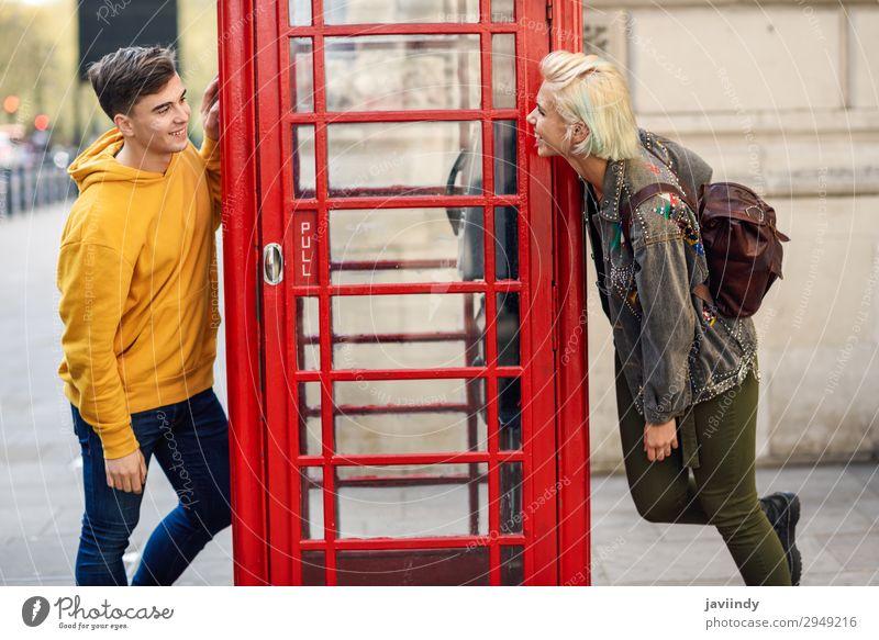 Junge Freunde in der Nähe einer klassischen britischen roten Telefonzelle. Lifestyle Ferien & Urlaub & Reisen Tourismus Sightseeing Mensch maskulin feminin