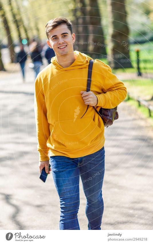 Junger Stadtmensch, der auf der Straße in einem Stadtpark in London spaziert. Lifestyle Glück Ferien & Urlaub & Reisen Telefon PDA Technik & Technologie Mensch