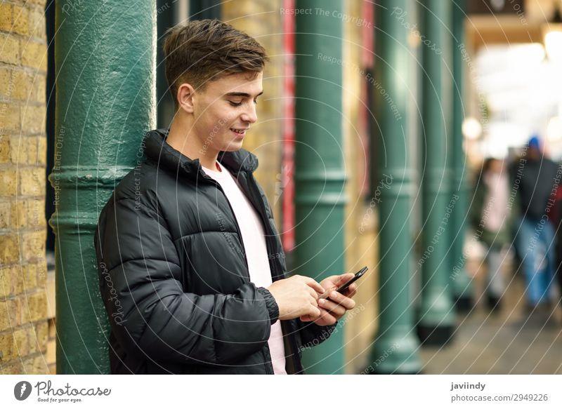 Junger Stadtmensch mit Smartphone im urbanen Hintergrund. Lifestyle Stil Glück Telefon PDA Technik & Technologie Mensch maskulin Junger Mann Jugendliche