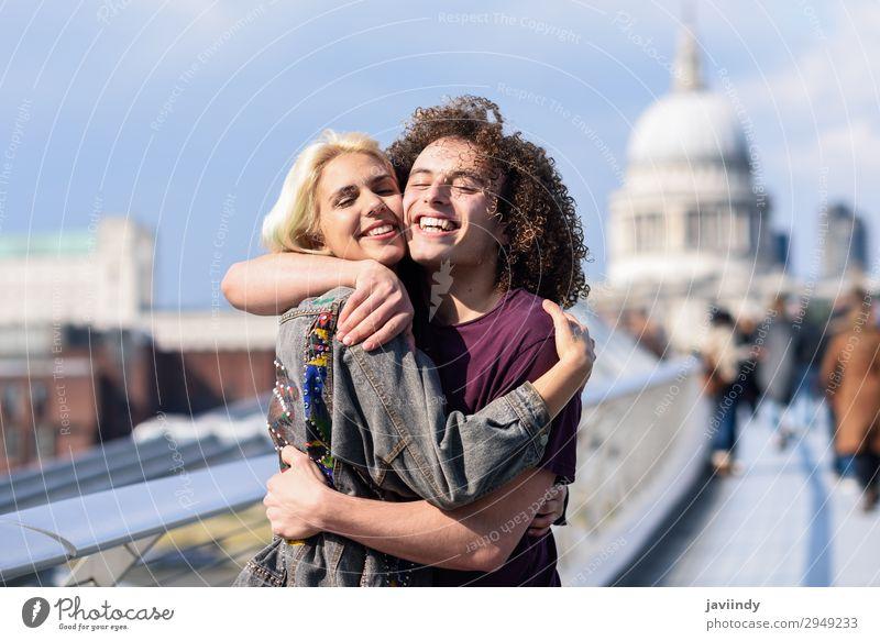 Ein glückliches Paar umarmt sich an der Millennium Bridge, River Thames, London. Freude Glück Mensch maskulin feminin Junge Frau Jugendliche Junger Mann