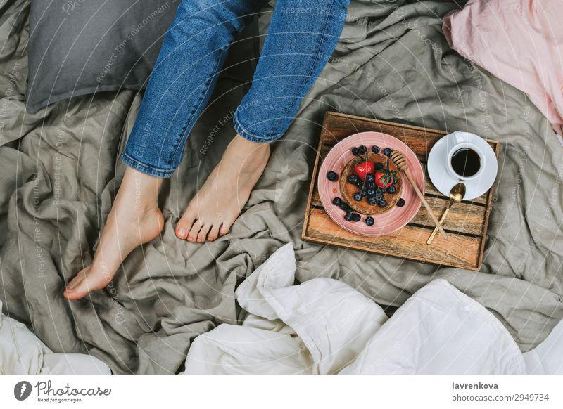 Frau auf einem Bett sitzend mit gesundem Frühstück oben Bettwäsche Schlafzimmer Blaubeeren Schalen & Schüsseln Jeansstoff Diät gesichtslos frisch Junge Frau