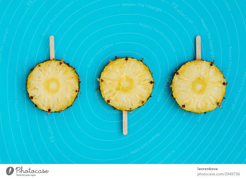 Ananaskreise auf hölzernen Eisstielen Dessert süß Bonbon Lebensmittel Gesunde Ernährung Speise Foodfotografie Stock Holz blau türkis zyan Frucht Stieleis frisch