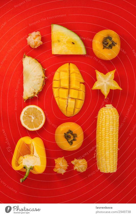 verschiedene gelbe und orange Früchte und Gemüse auf rot Mango Frucht flach legen Paprika Klingel Corny Zitrone Zitrusfrüchte frisch Gesundheit