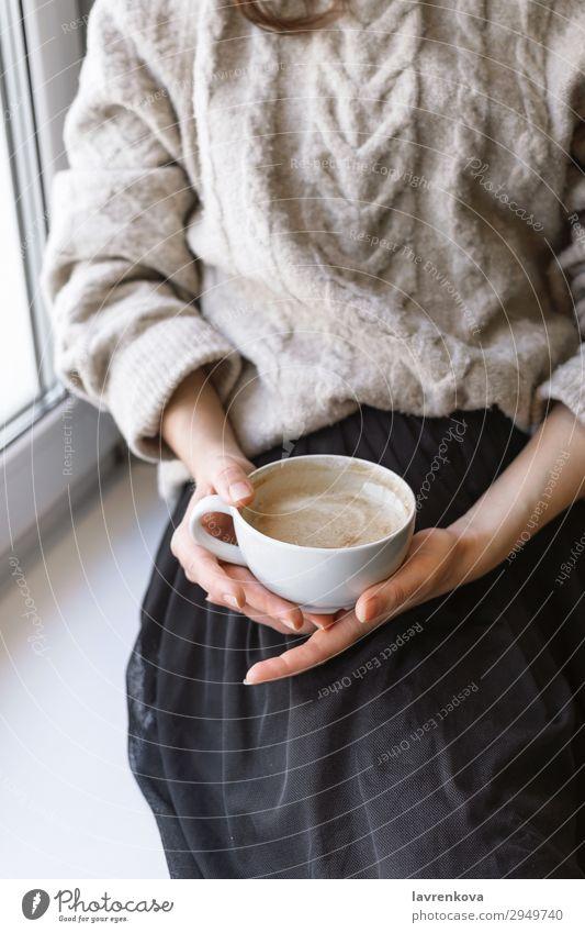 Damenhaltebecher mit Latte vor dem Fenster Herbst Winter Erholung Pullover Frühstück Innenaufnahme Hand Tasse Becher Wärme gemütlich Café Nahaufnahme Kaffee