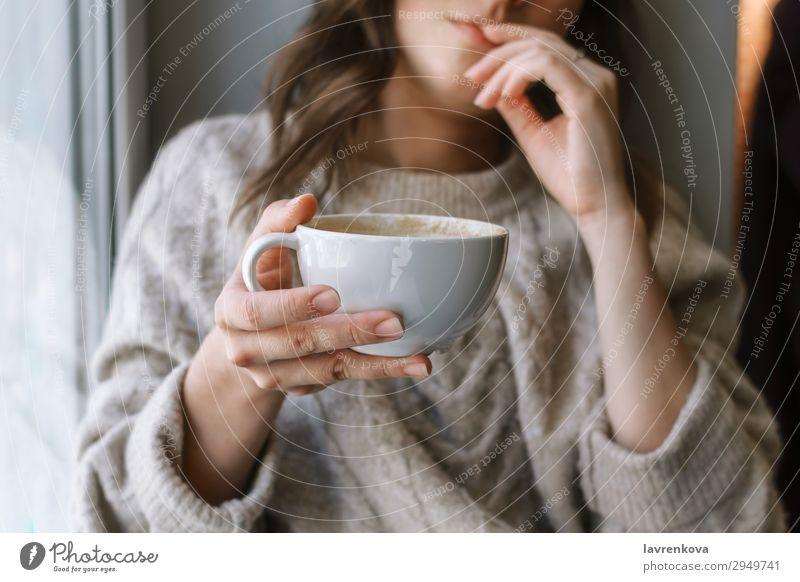 Damenhaltebecher mit Latte vor dem Fenster Selektiver Fokus Café Nahaufnahme Kaffee Tasse Getränk trinken Frau Schwache Tiefenschärfe Junge Frau heimwärts heiß