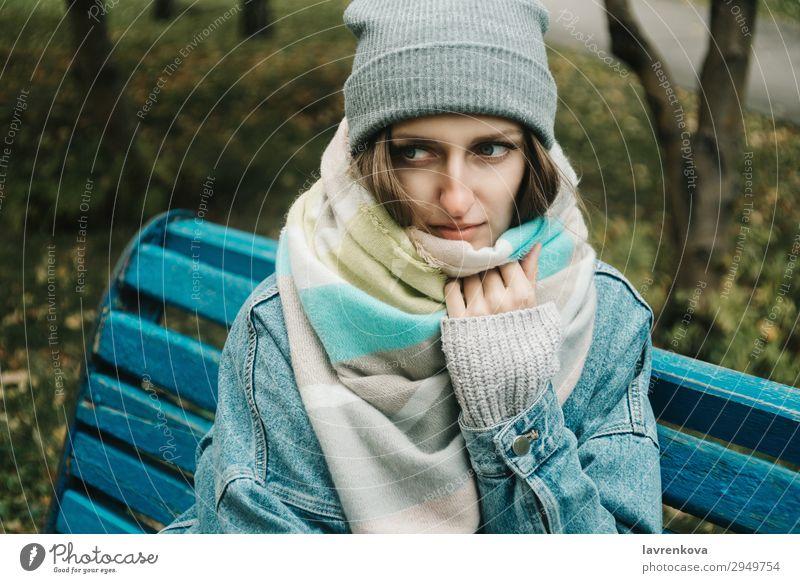 junge erwachsene Frau, die auf einer Bank sitzt, die mit einem Schal umwickelt ist. Erwachsene Einsamkeit attraktiv Herbst schön Kaukasier kalt Jeansstoff Wald