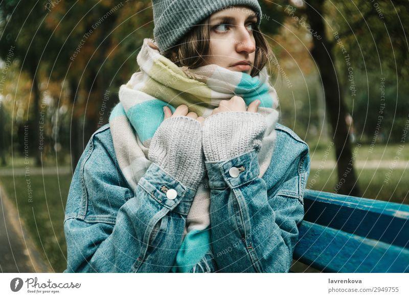 junge erwachsene Frau, die auf einer Bank sitzt, die mit einem Schal umwickelt ist. Einsamkeit Baum Hut Jeansstoff kalt Außenaufnahme Model Behaarung Erwachsene