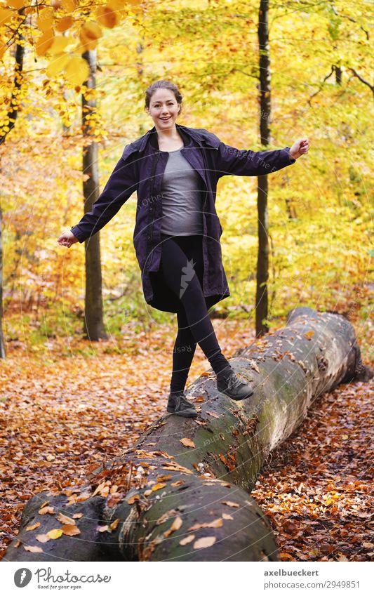 junge Frau balanciert auf Baumstamm im Herbstwald Mensch Natur Jugendliche Junge Frau Freude Wald 18-30 Jahre Lifestyle Erwachsene feminin Glück