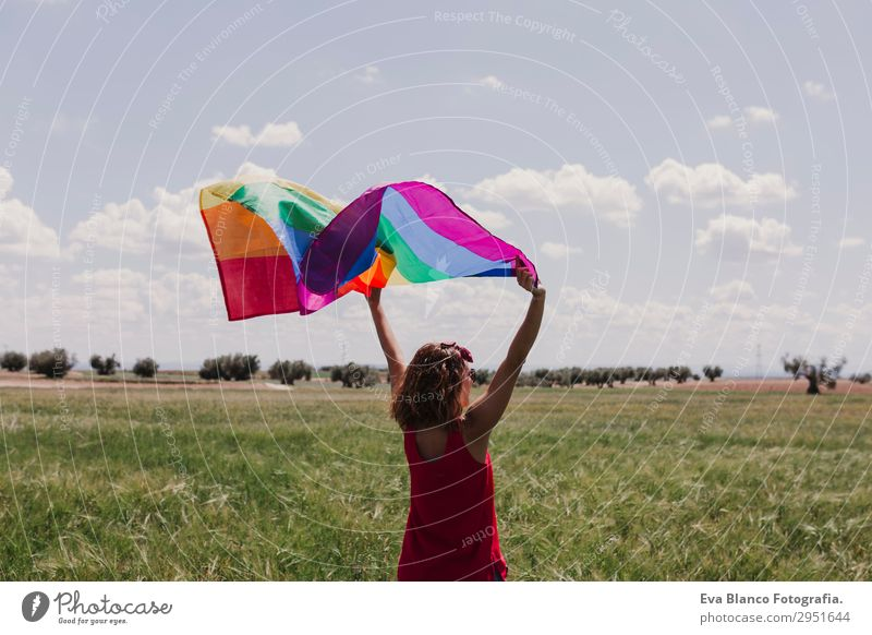 Frau hält die Gay Rainbow Flag auf einer grünen Wiese im Freien. Lifestyle Freude Glück Freizeit & Hobby Freiheit Sommer Sonne Hochzeit Mensch feminin