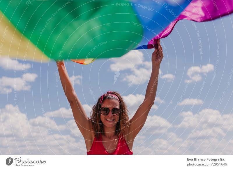 Frau hält die Gay Rainbow Flag über dem blauen Himmel im Freien. Lifestyle Freude Glück Freizeit & Hobby Freiheit Sommer Sonne Hochzeit Mensch feminin