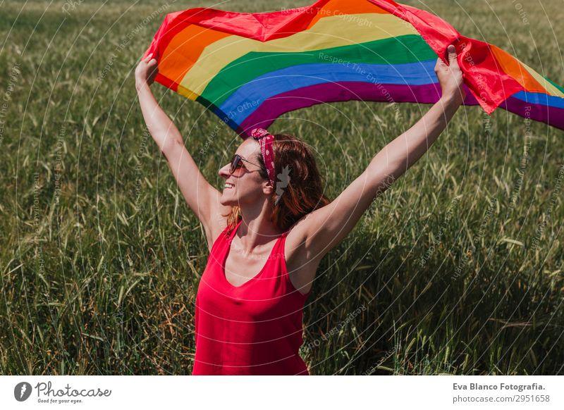 Frau hält die Gay Rainbow Flag auf einer grünen Wiese im Freien. Lifestyle Freude Glück Freiheit Sommer Sonne Hochzeit Mensch feminin Homosexualität Junge Frau
