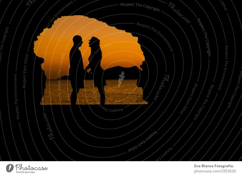 Silhouette eines jungen Paares, das am Strand bei Sonnenuntergang liebt. Spielen Ferien & Urlaub & Reisen Meer Insel Flirten Junge Frau Jugendliche Junger Mann
