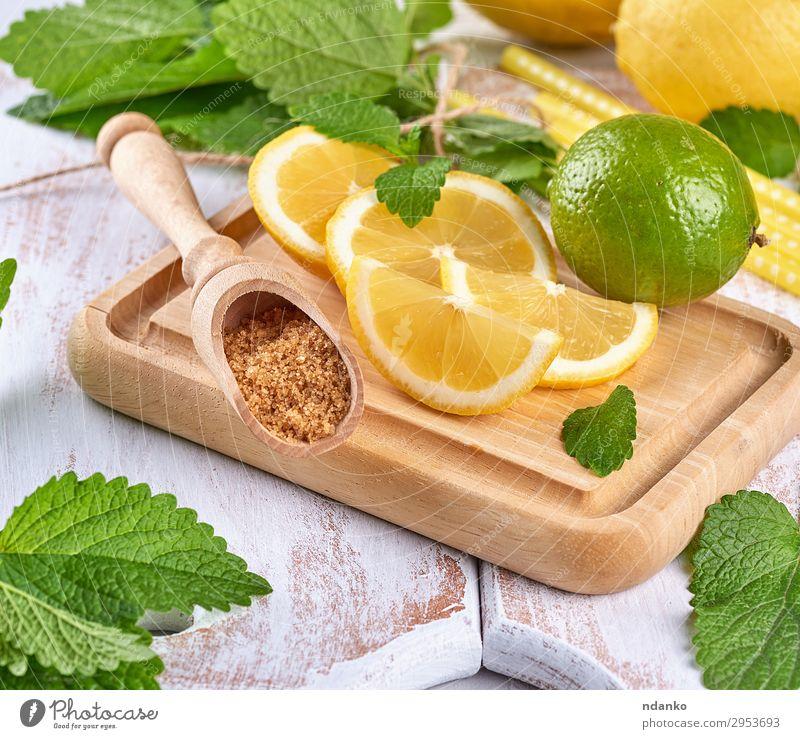 reife gelbe Zitronen und Limetten, brauner Zucker Frucht Kräuter & Gewürze Limonade Saft Löffel Sommer Tisch Blatt Tube Holz machen frisch oben saftig grün weiß