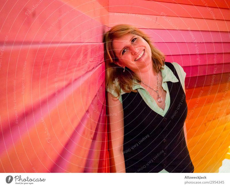 junge Frau lehnt glücklich an einer bunten Holzwand Innenaufnahme 1 Mensch Junge Frau Kunstlicht Porträt Blick nach vorn Blick in die Kamera blond Zaun Barriere