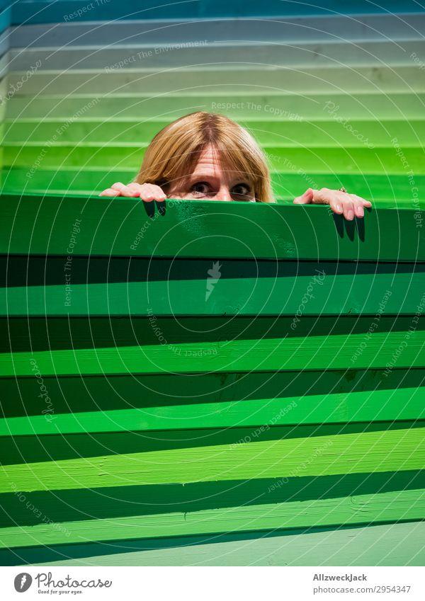 Junge Frau schaut vorsichtig über einen Holzzaun Kopf Zaun Grenze spionieren Blick beobachten Vorsicht grün Schüchternheit zögern hervorgucken drüberschauen