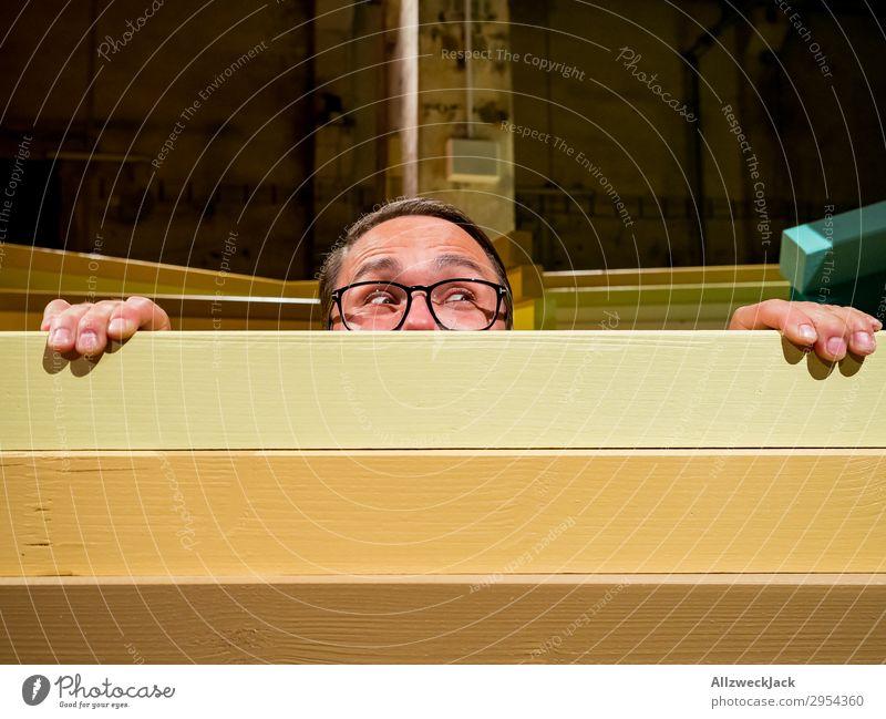 Junger Mann schaut neugierig über eine Absperrung Innenaufnahme 1 Mensch Kunstlicht Porträt Blick nach vorn Blick in die Kamera Brille Zaun Barriere Holzzaun