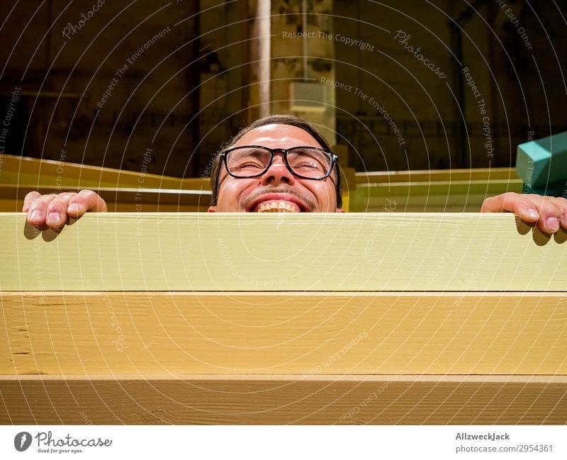 Junger Mann schaut über eine Absperrung Innenaufnahme 1 Mensch Kunstlicht Porträt Blick nach vorn Blick in die Kamera Brille Zaun Barriere Holzzaun spionieren