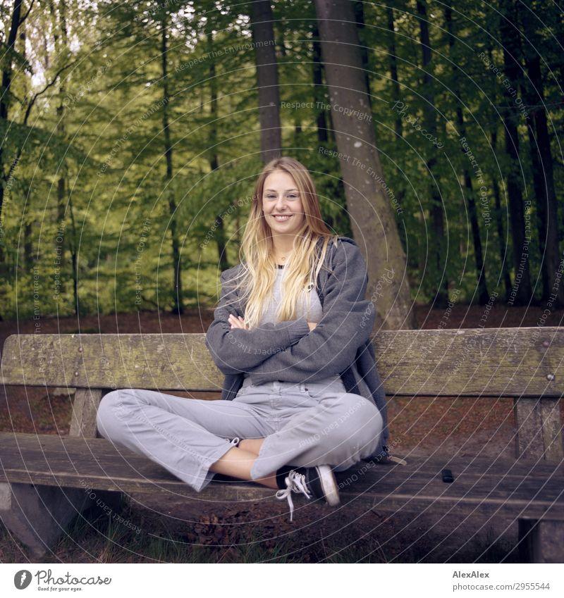 Junge Frau sitzt im Schneidersitz auf einer Bank in einem Wald und lächelt in die Kamera Freude schön Wellness Leben Ausflug Jugendliche 18-30 Jahre Erwachsene