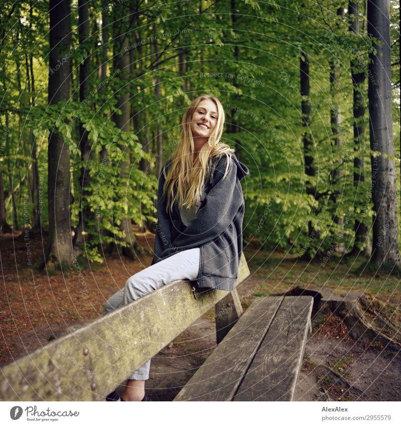 Junge Frau sitzt lächelnd auf einer Bank in einem Wald Stil Freude schön Leben harmonisch Jugendliche 18-30 Jahre Erwachsene Natur Landschaft Schönes Wetter