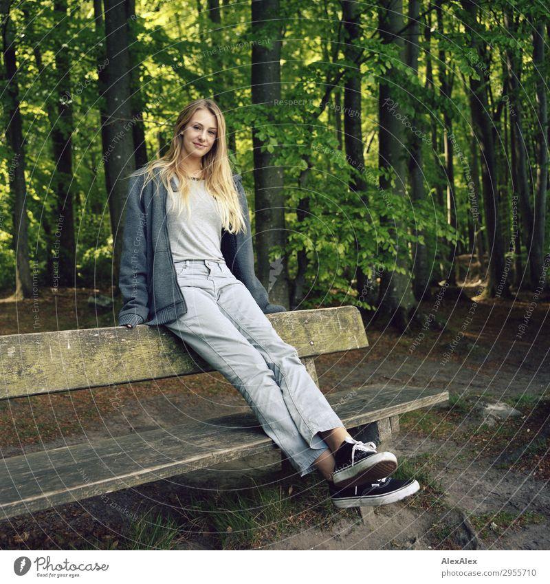 Junge Frau sitzt auf einer Bank in einem Wald Freude schön Wellness Leben Jugendliche 18-30 Jahre Erwachsene Natur Landschaft Schönes Wetter Jeanshose Jacke