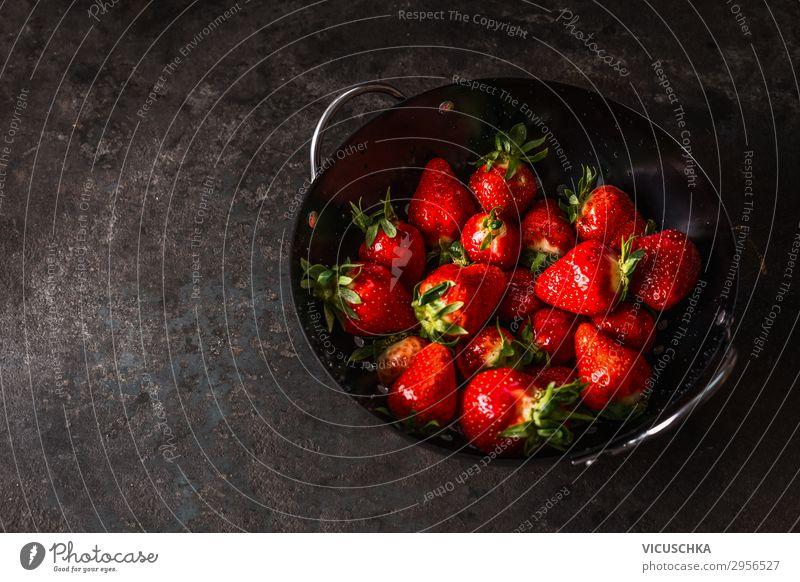 Leckere Erdbeeren in schwarzer Siebschale auf dunklem, rustikalem Küchentisch. Raum kopieren. Saisonale Bio-Lebensmittel. Gesundes Essen und Kochen