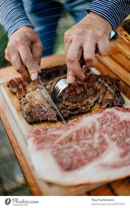 Hände eines Mannes, der gegrilltes Kobe-Rindfleisch in Scheiben schneidet Barbecue grillen Beefsteak Küche kulinarisch geschnitten Schneiden Feinwäsche