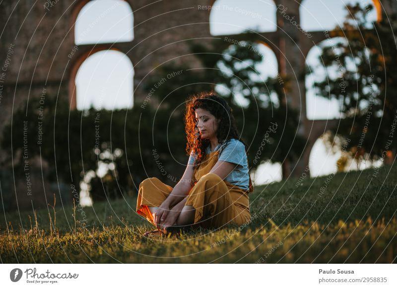 Junge Frau ruht sich bei Sonnenuntergang aus Lifestyle Wohlgefühl Erholung Meditation Mensch feminin Jugendliche 1 18-30 Jahre Erwachsene Natur Sommer Park