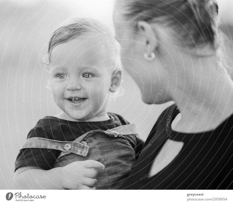 Schwarz-Weiß-Aufnahme der jungen Mutter trägt und Blick auf freudige ein Jahr Baby Mädchen mit Liebe. Glückliche Mutterschaft Stil Freude Kind Mensch Frau