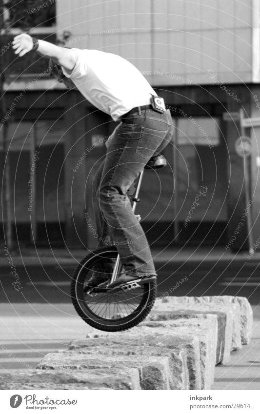 Einrad Mann springen Stein Zufriedenheit Fahrrad Jeanshose hüpfen Fahrradfahren Einradfahren