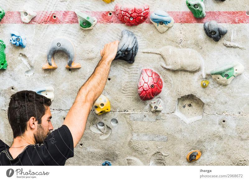 Mann übt Klettern an einer künstlichen Wand in Innenräumen. Lifestyle Freude Freizeit & Hobby Sport Bergsteigen maskulin Junger Mann Jugendliche Erwachsene Hand