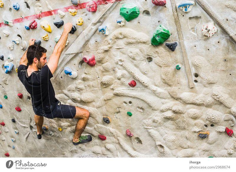 Mann, der an einer künstlichen Wand in der Halle Klettern übt. Aktiver Lebensstil und Boulderkonzept. aktiv schwarz Felsbrocken Bouldern Kreide Herausforderung