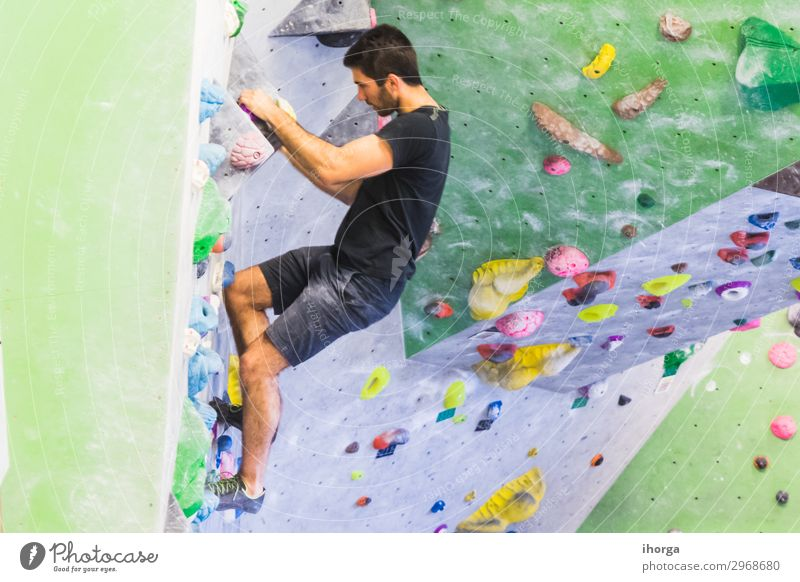 Mann übt Klettern an einer künstlichen Wand in Innenräumen. Lifestyle Freude Freizeit & Hobby Sport Bergsteigen maskulin Junger Mann Jugendliche Erwachsene 1