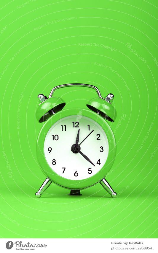 Schließen Sie einen Wecker auf grünem Hintergrund. Papier Uhr Zifferblatt Uhrenzeiger Metall Zeitpunkt Frist retro Farbfoto mehrfarbig Studioaufnahme